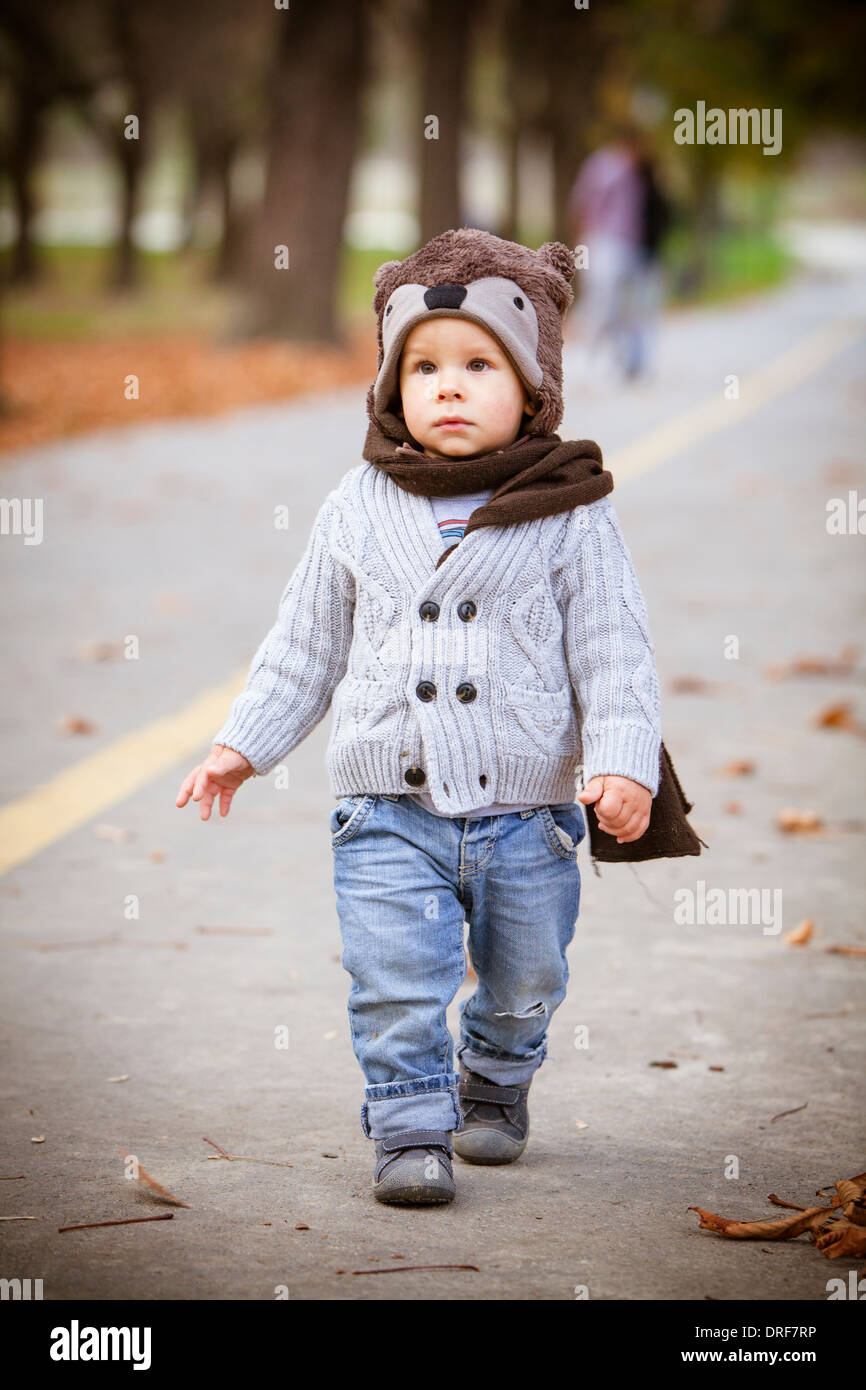 Toddler with cap and scarf walking on a street, Osijek, Croatia - Stock Image