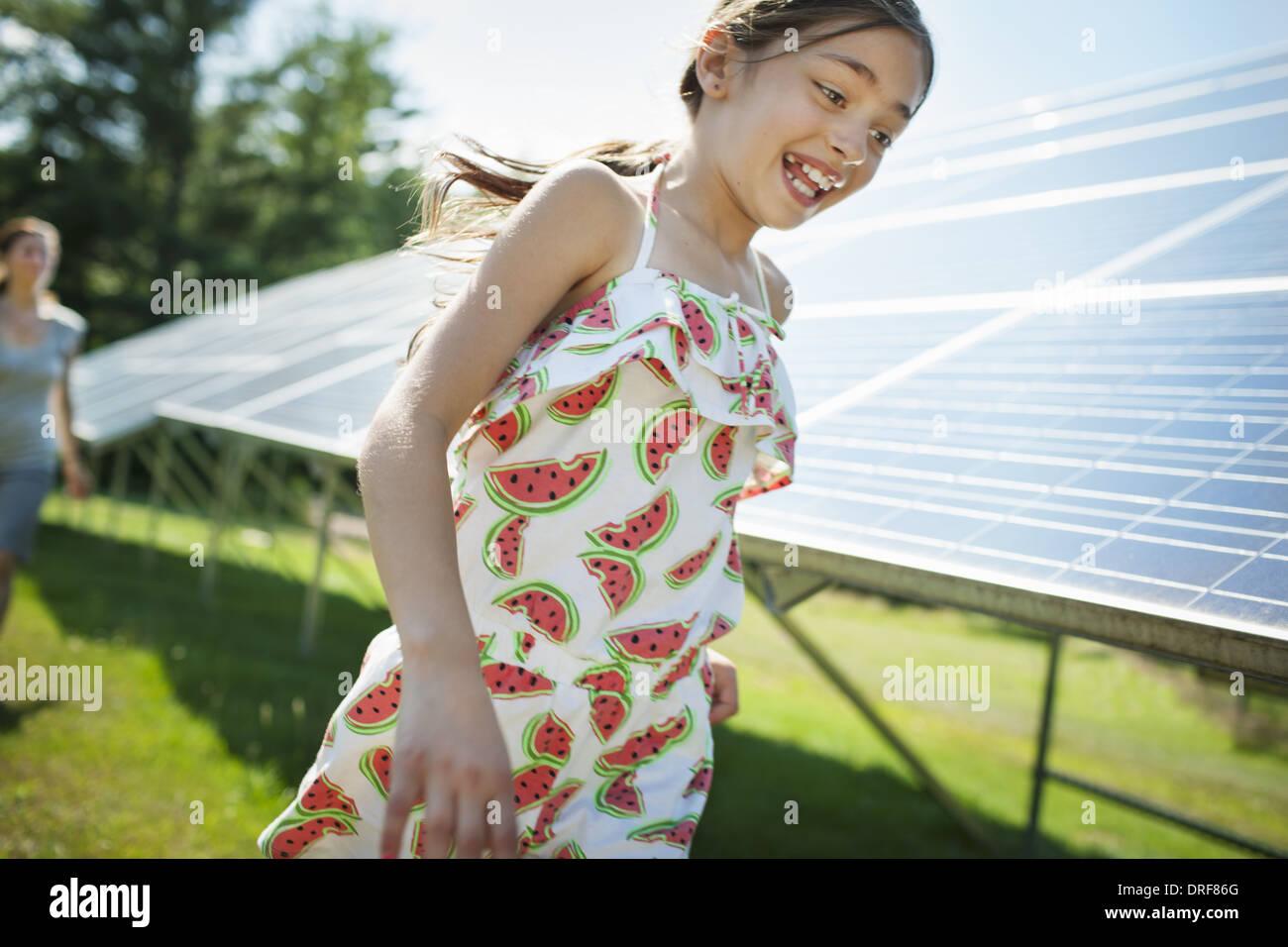 New York state USA child mother beside solar panels farm USA - Stock Image