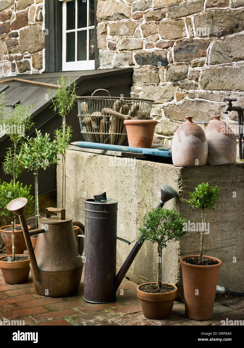 Maryland USA collection of old watering cans clay pots plants - Stock Image