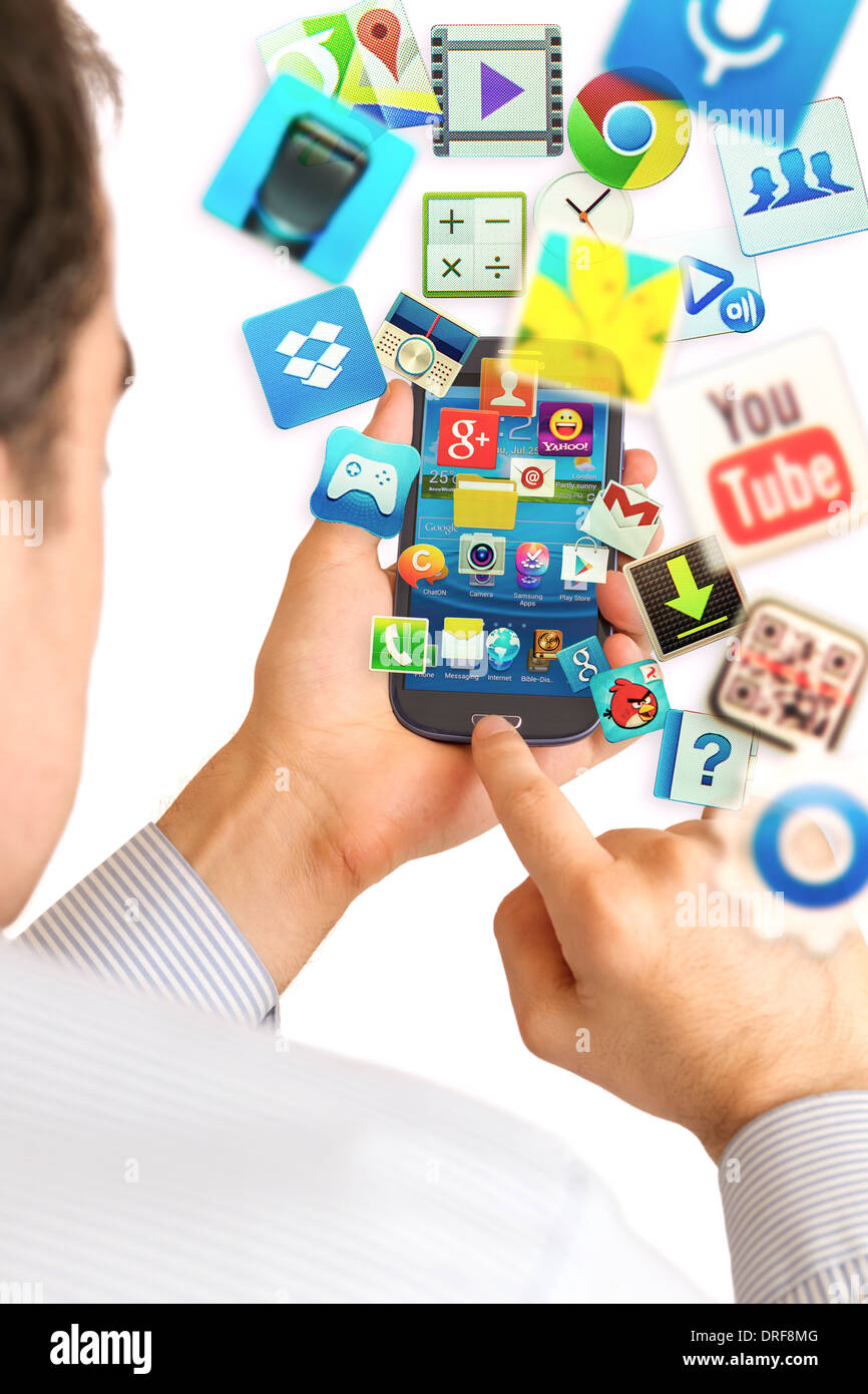 Hand holding Samsung Galaxy S3 displaying homescreen and apps flying from smartphone. - Stock Image
