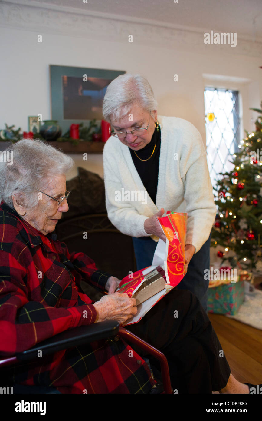 Detroit, Michigan - Dorothy Newell, 99, opens a Christmas present with the help of her daughter, Susan Newell, 65. - Stock Image