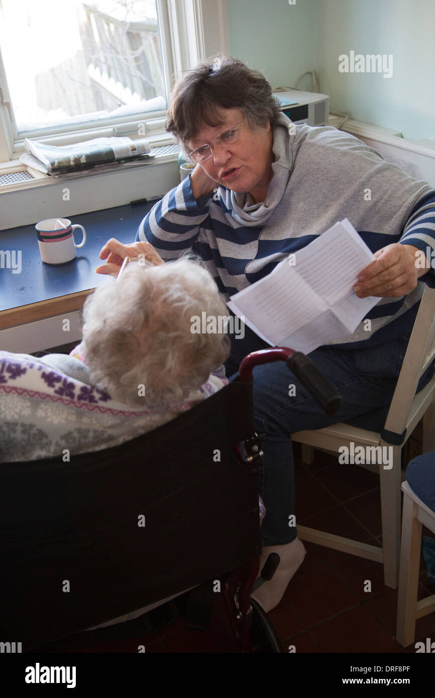 Woman reads letter to her blind aunt - Stock Image