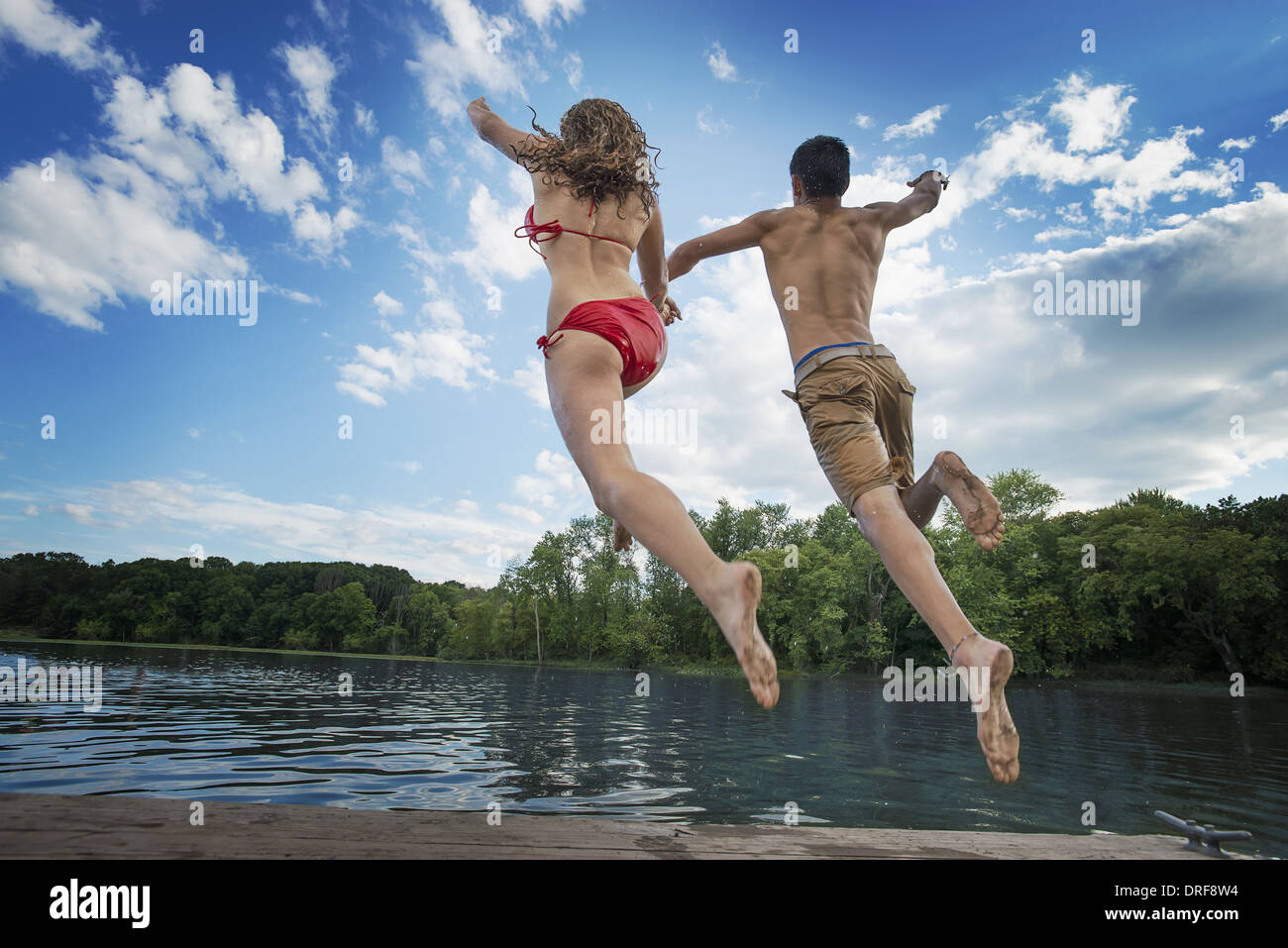 New York state USA boy and girl leaping off jetty into lake river Stock Photo