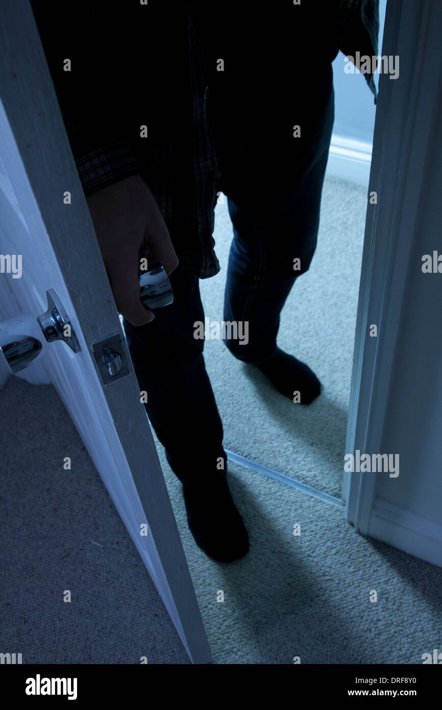 Silhouette of a man entering a darkened room. - Stock Image
