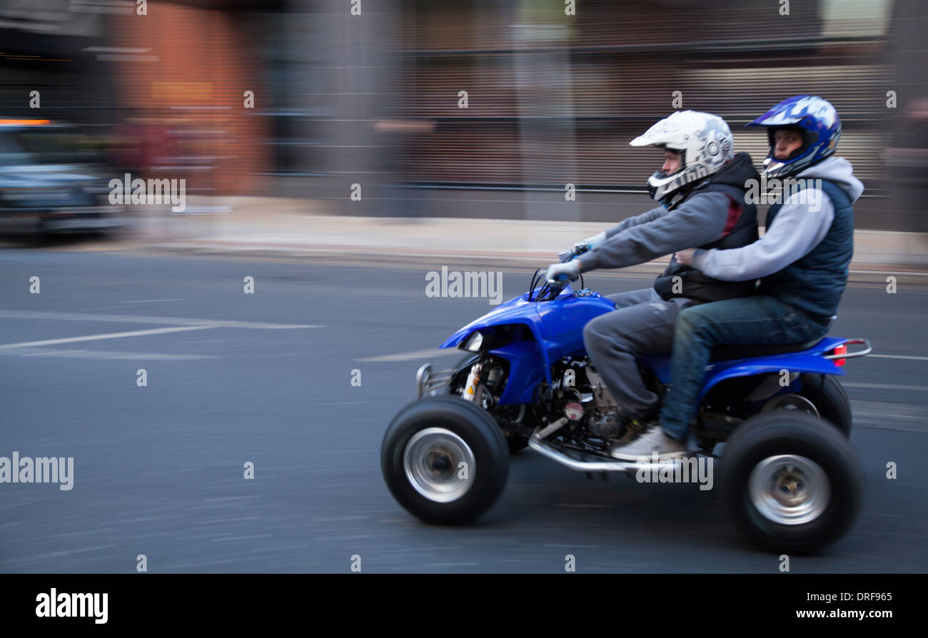Street Legal _ Youths on Quad Bike speeding down London Road, Manchester City Centre, UK, Europe, UK - Stock Image