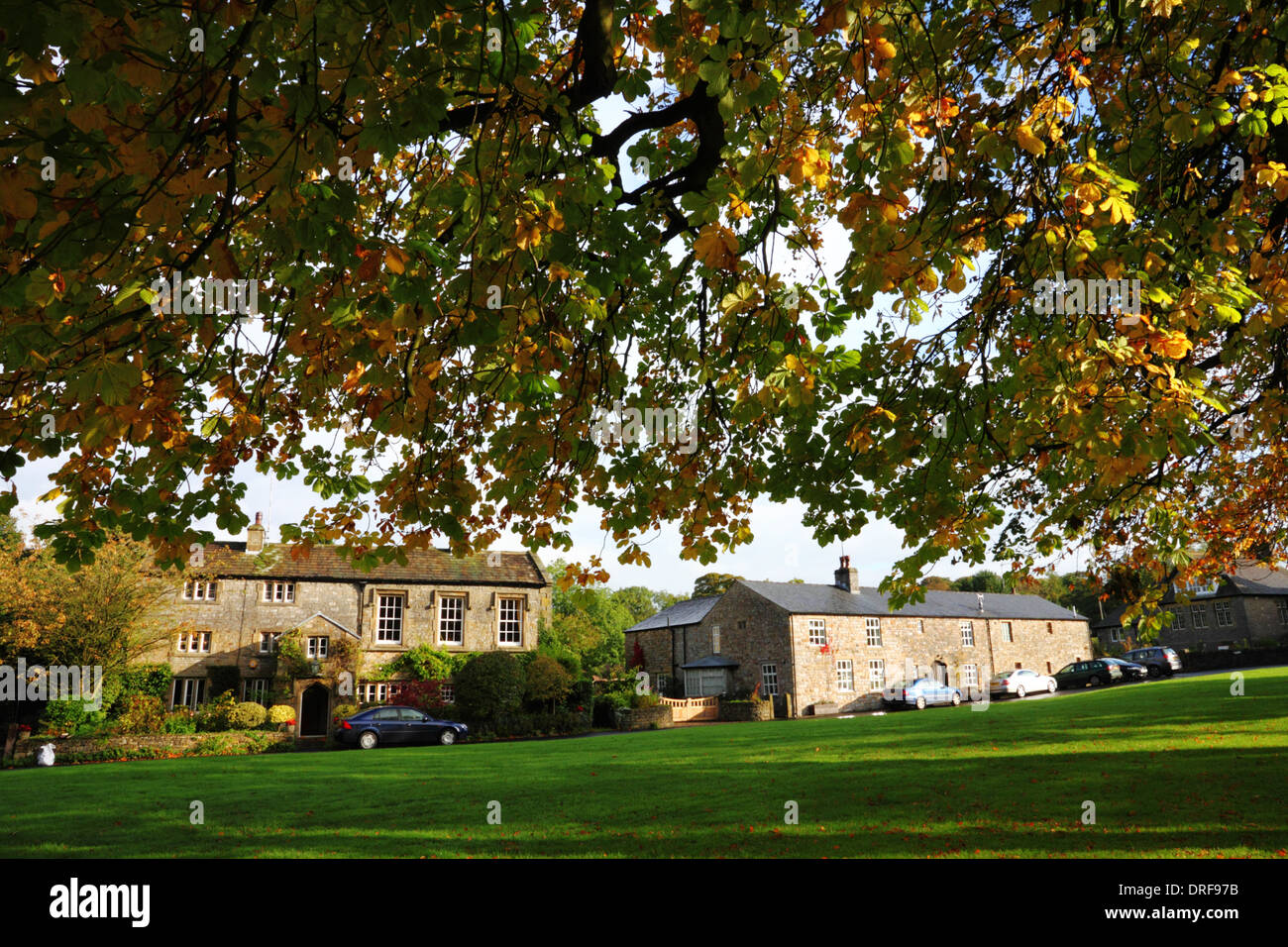 A village green with houses under a canopy of branches with autumn colours. - Stock Image