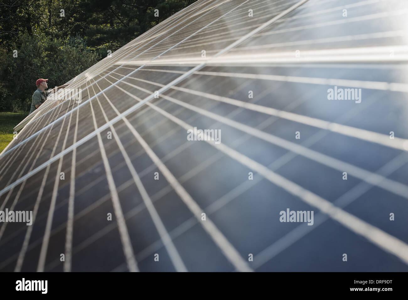 New York state USA man inspecting surface solar panel installation - Stock Image