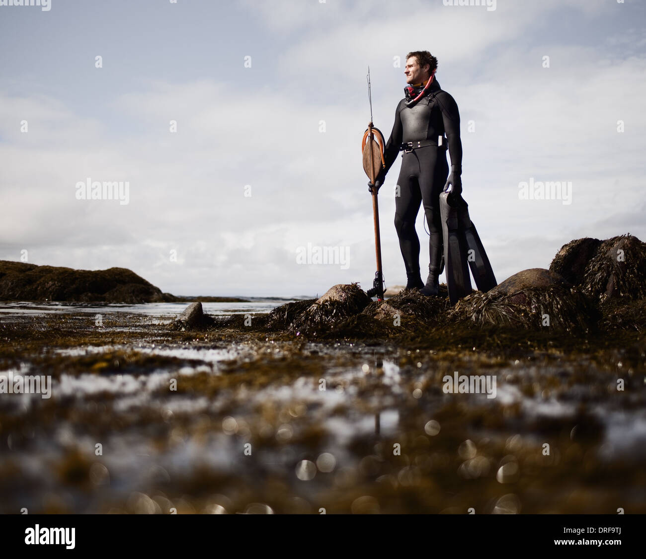 USA man in wetsuit standing on shore with large spear - Stock Image