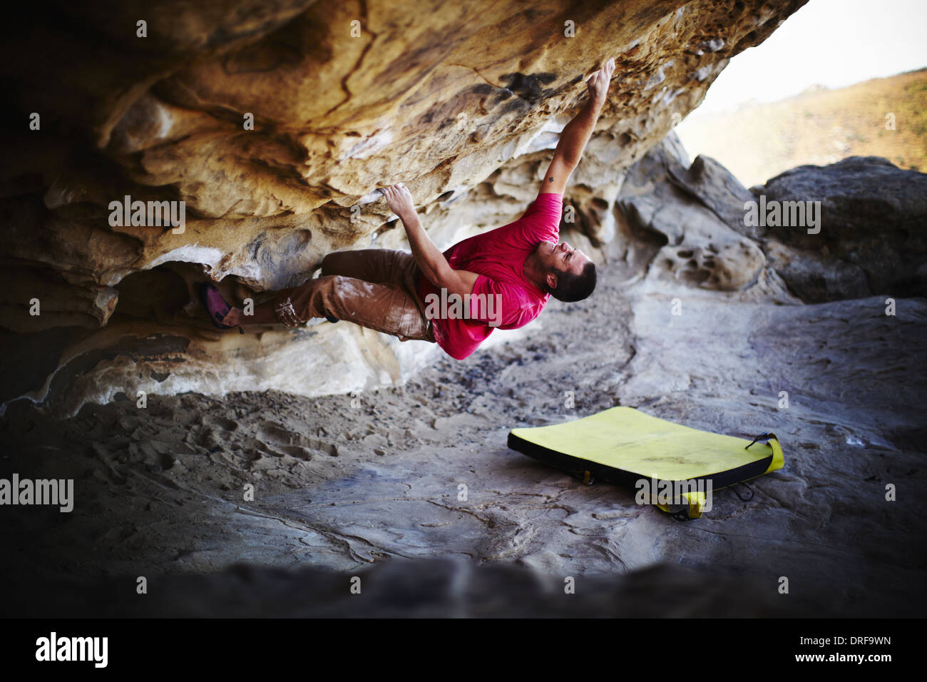 USA man free climbing on the overhang of rock face - Stock Image
