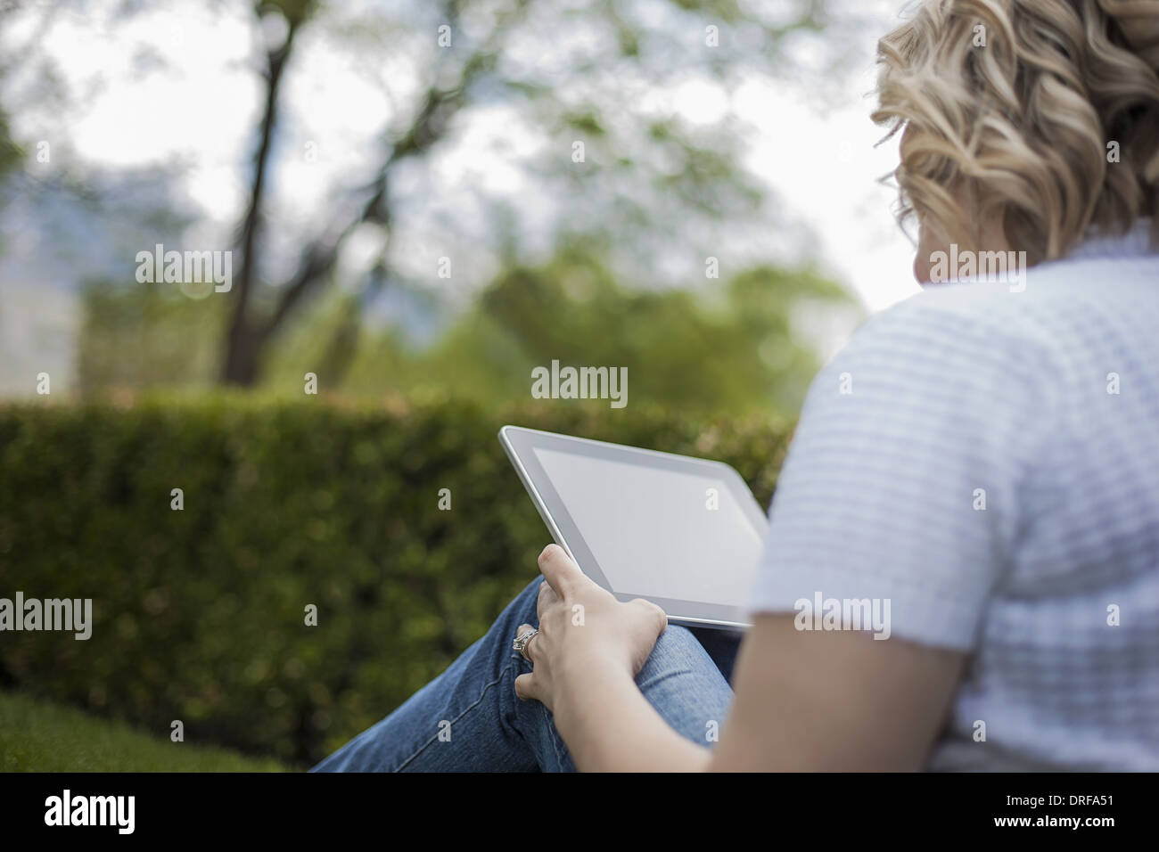 Utah USA young woman reading using handheld tablet - Stock Image