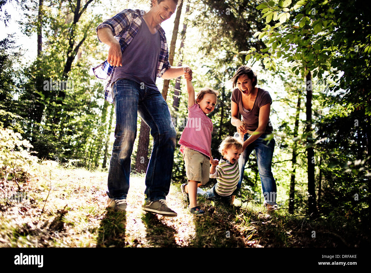 Family and two children playing in forest having fun bavaria germany