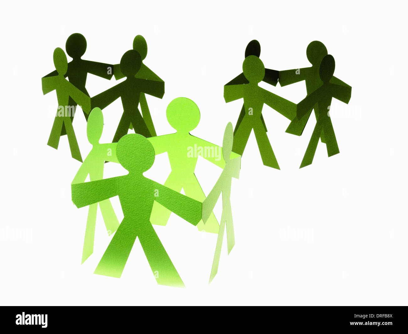 Papercuts paper cut out people with joined hands - Stock Image