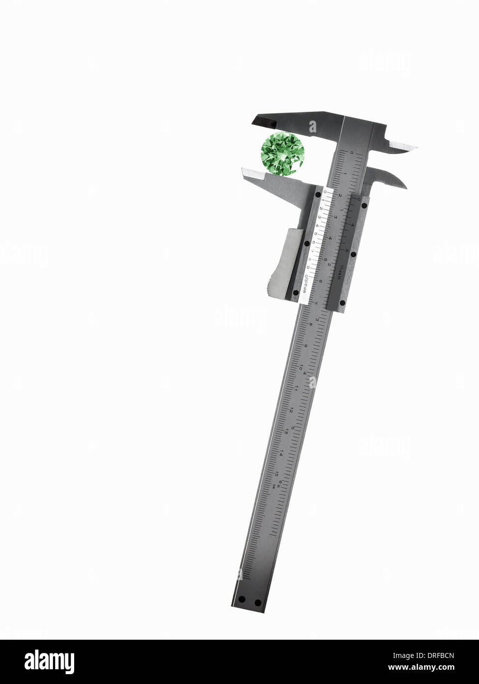 caliper measuring green crystal cut gemstone - Stock Image