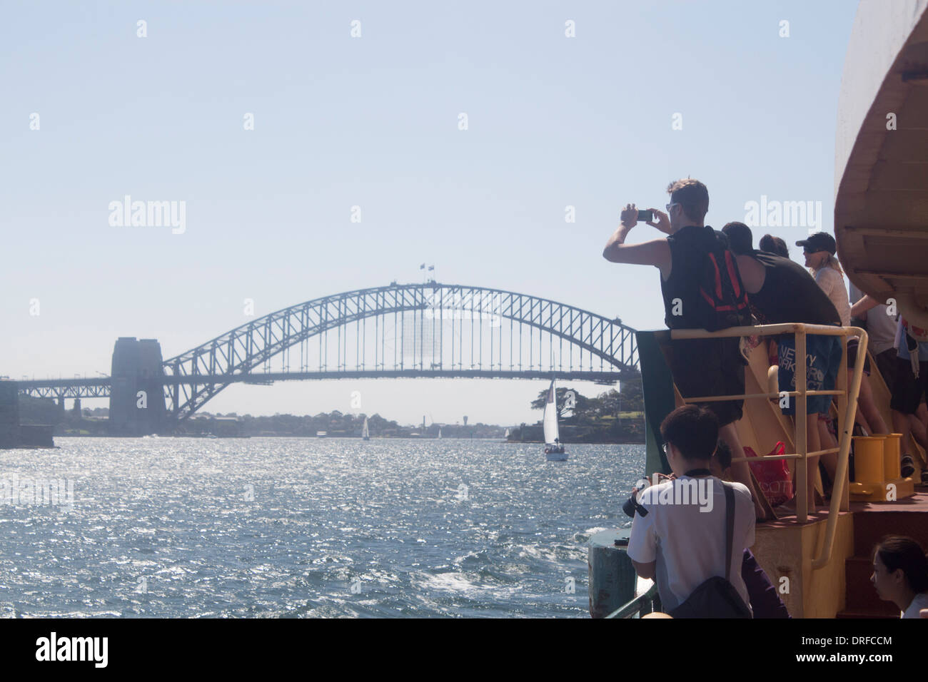 People photographing Sydney Harbour Bridge from ferry with cameraphones and smartphones Sydney New South Wales NSW Australia - Stock Image