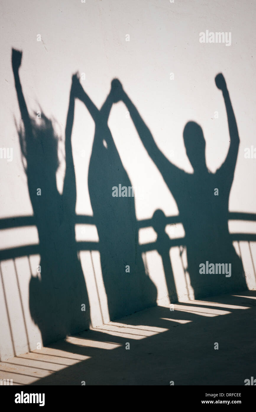 Creative photo of happy people shadows on white wall holding hands - Stock Image