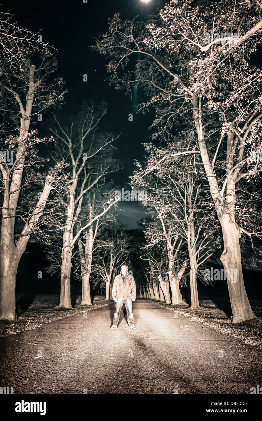 Scary horror person standing in night landscape - Stock Image