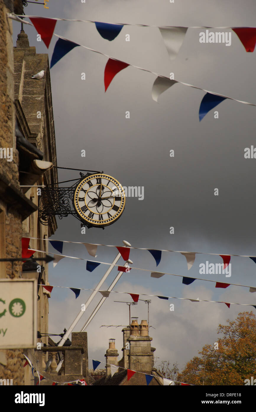 Picture taken in Corsham High Street in Wiltshire showing the clock and bunting under a stormy sky Stock Photo