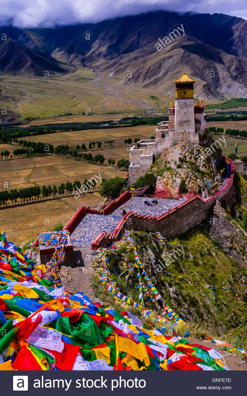 Thousands of prayer flags drape a mountain above the Yambulakhang Palace, Tibet, China. The five colors of the prayer flags represent the five elements: blue for sky, white for wind, red for fire, green for water, and yellow for earth. - Stock Image