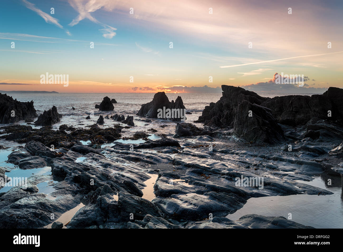 Low tide and sunrise at the beach at Looe in Cornwall - Stock Image