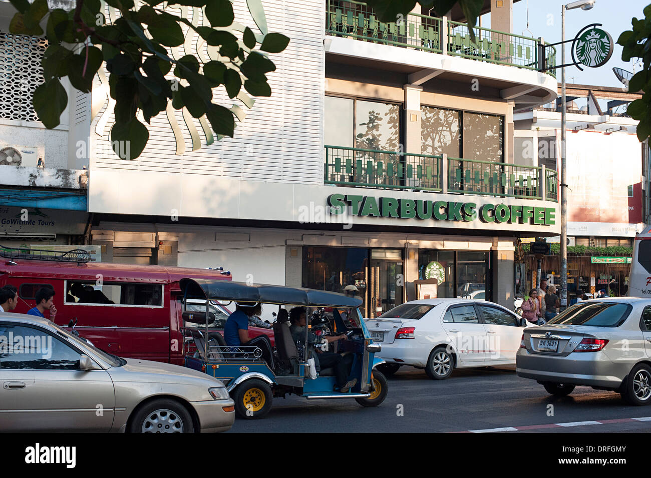 Urban busy city road with Starbucks Coffee shop and big sign. Chiang Mai, Thailand - Stock Image