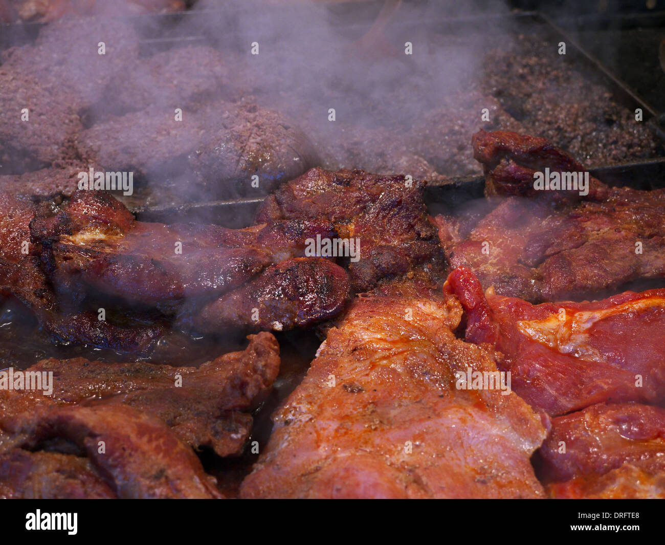 Beef and pork grilling in an outdoor stall at the Christmas markets in Krakow, Poland - Stock Image