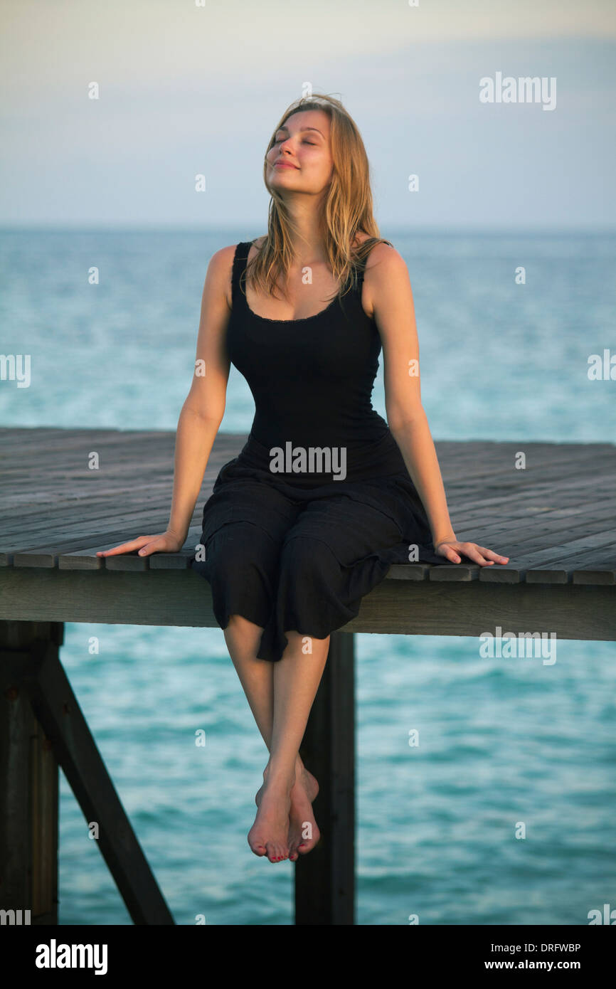 Young woman in sundress relaxes on a boardwalk, Lankayan Island, Borneo, Malaysia - Stock Image