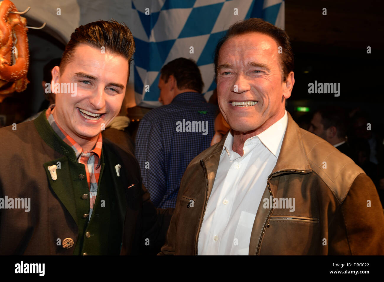 Kitzbuehel, Austria. 24th Jan, 2014. Former US governor and Hollywood actor Arnold Schwarzenegger (R) poses with singer Andreas Gabalier (L) at the Bavarian veal sausage party in the Stanglwirt bar near Kitzbuehel, Austria, 24 January 2014. Many celebrities came for the annual Austrian downhill ski race Hahnenkamm race in worldfamous skiing location. Photo: Felix Hoerhager/dpa/Alamy Live News - Stock Image