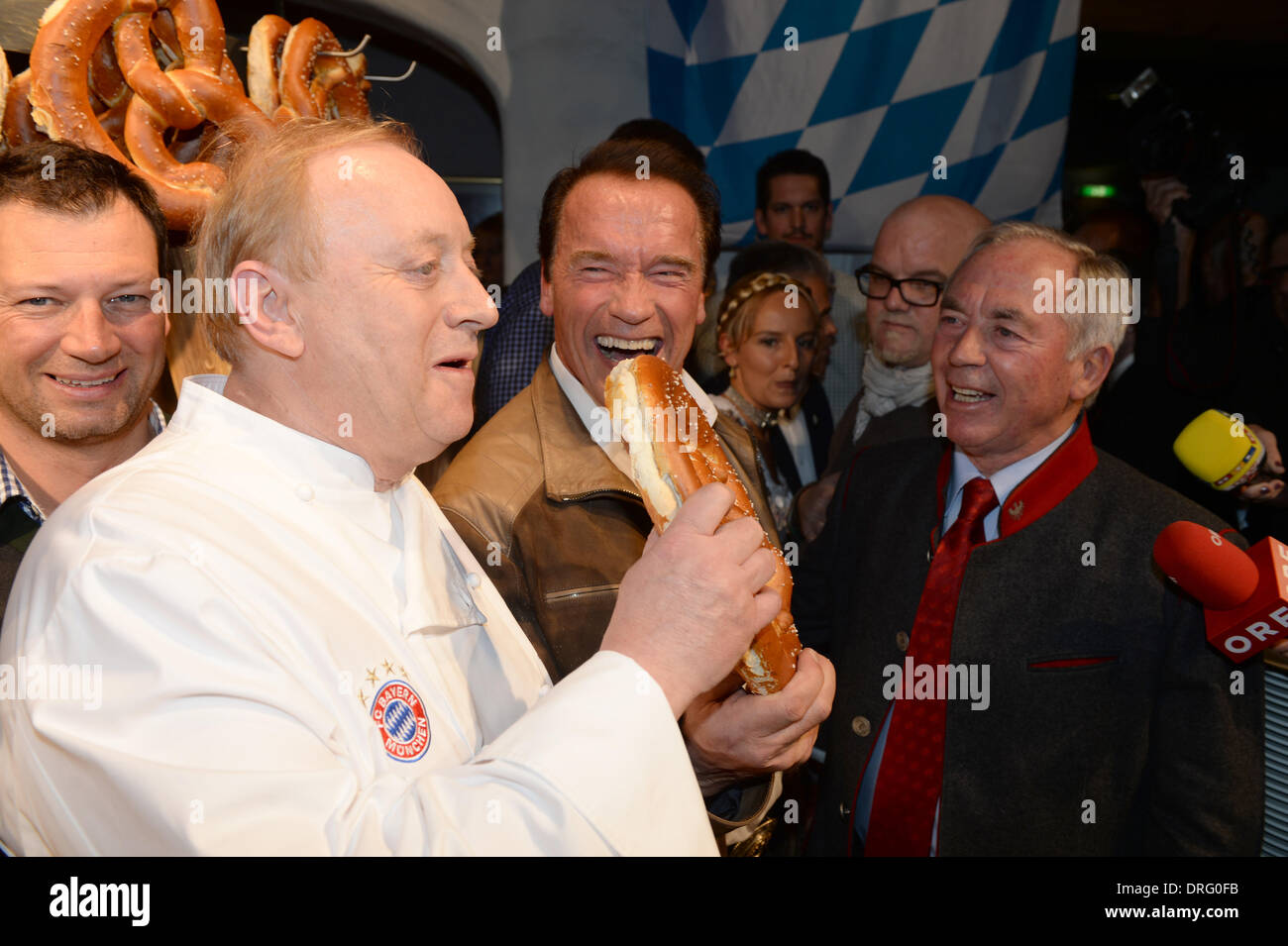Kitzbuehel, Austria. 24th Jan, 2014. Former US governor and Hollywood actor Arnold Schwarzenegger (C) feeds chef Alfons Schuhbeck (L) at the Bavarian veal sausage party in the Stanglwirt bar near Kitzbuehel, Austria, 24 January 2014. Many celebrities came for the annual Austrian downhill ski race Hahnenkamm race in worldfamous skiing location. Photo: Felix Hoerhager/dpa/Alamy Live News - Stock Image