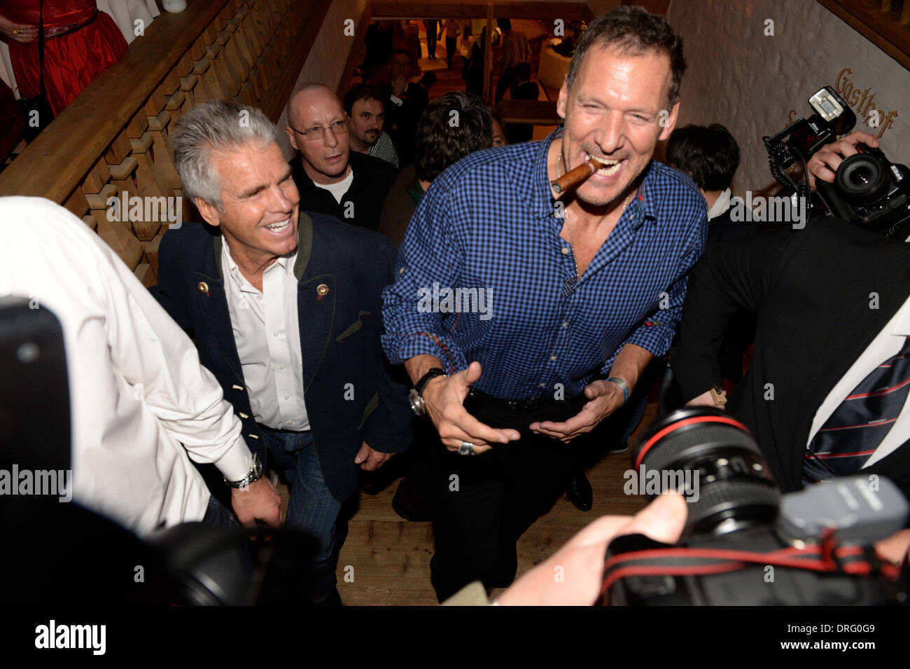 Kitzbuehel, Austria. 24th Jan, 2014. Actor Ralf Moeller (R) poses with a cigar at the Bavarian veal sausage party in the Stanglwirt bar near Kitzbuehel, Austria, 24 January 2014. Many celebrities came for the annual Austrian downhill ski race Hahnenkamm race in worldfamous skiing location. Photo: Felix Hoerhager/dpa/Alamy Live News - Stock Image