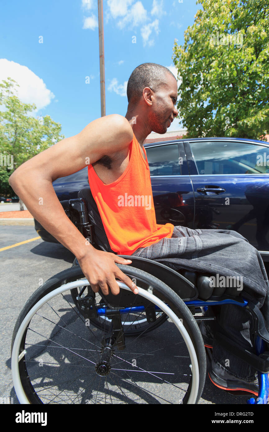 Man with spinal meningitis in wheelchair about to enter automobile - Stock Image