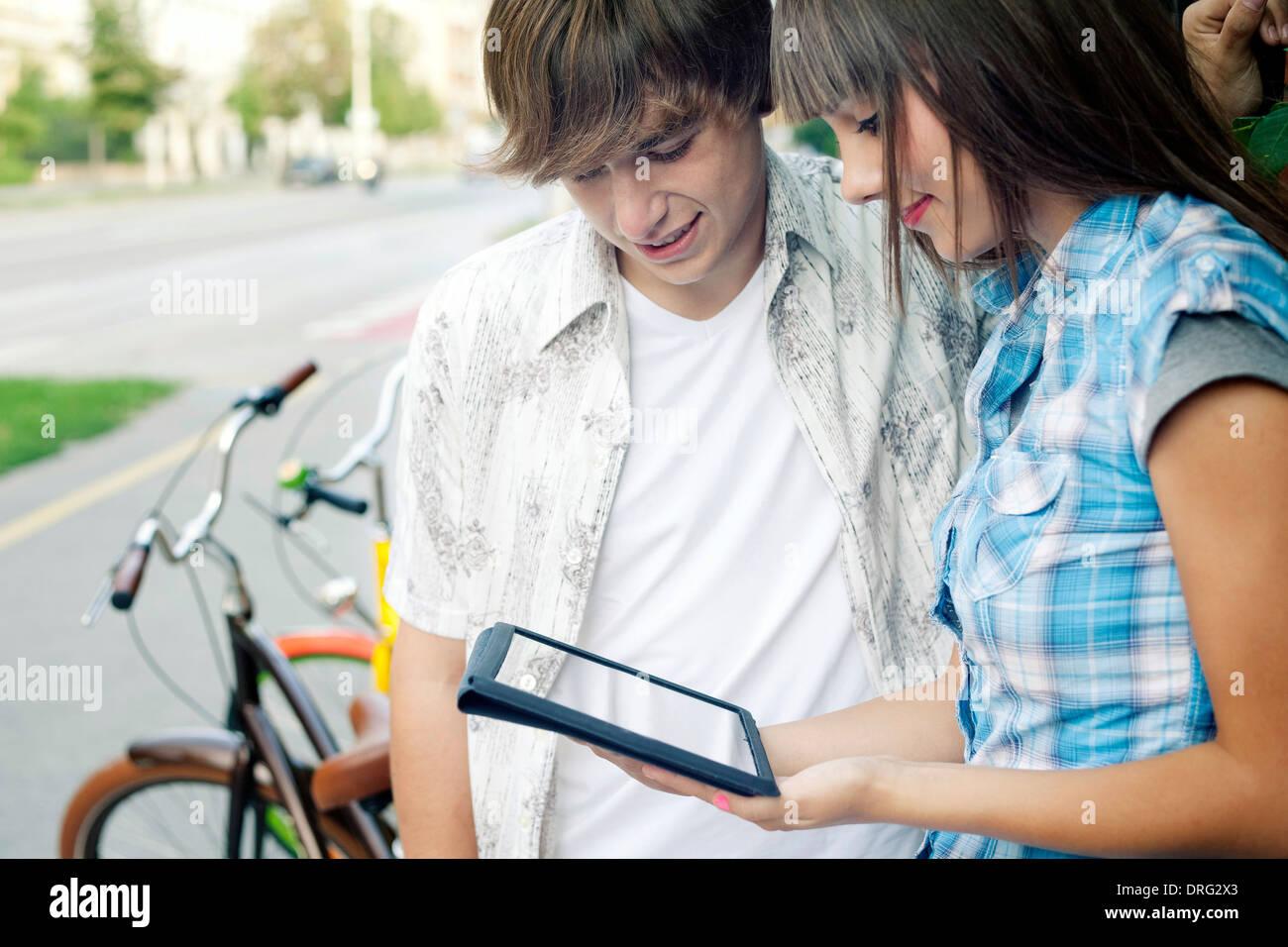 Young couple using digital tablet outdoors, Osijek, Croatia - Stock Image