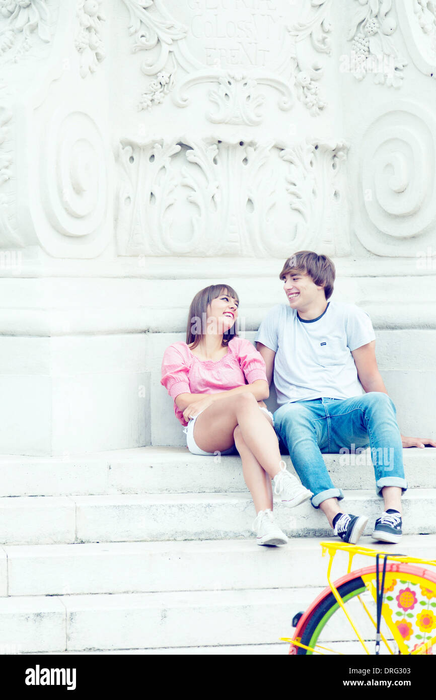 Young couple sitting together, leaning against statue, Osijek, Croatia - Stock Image
