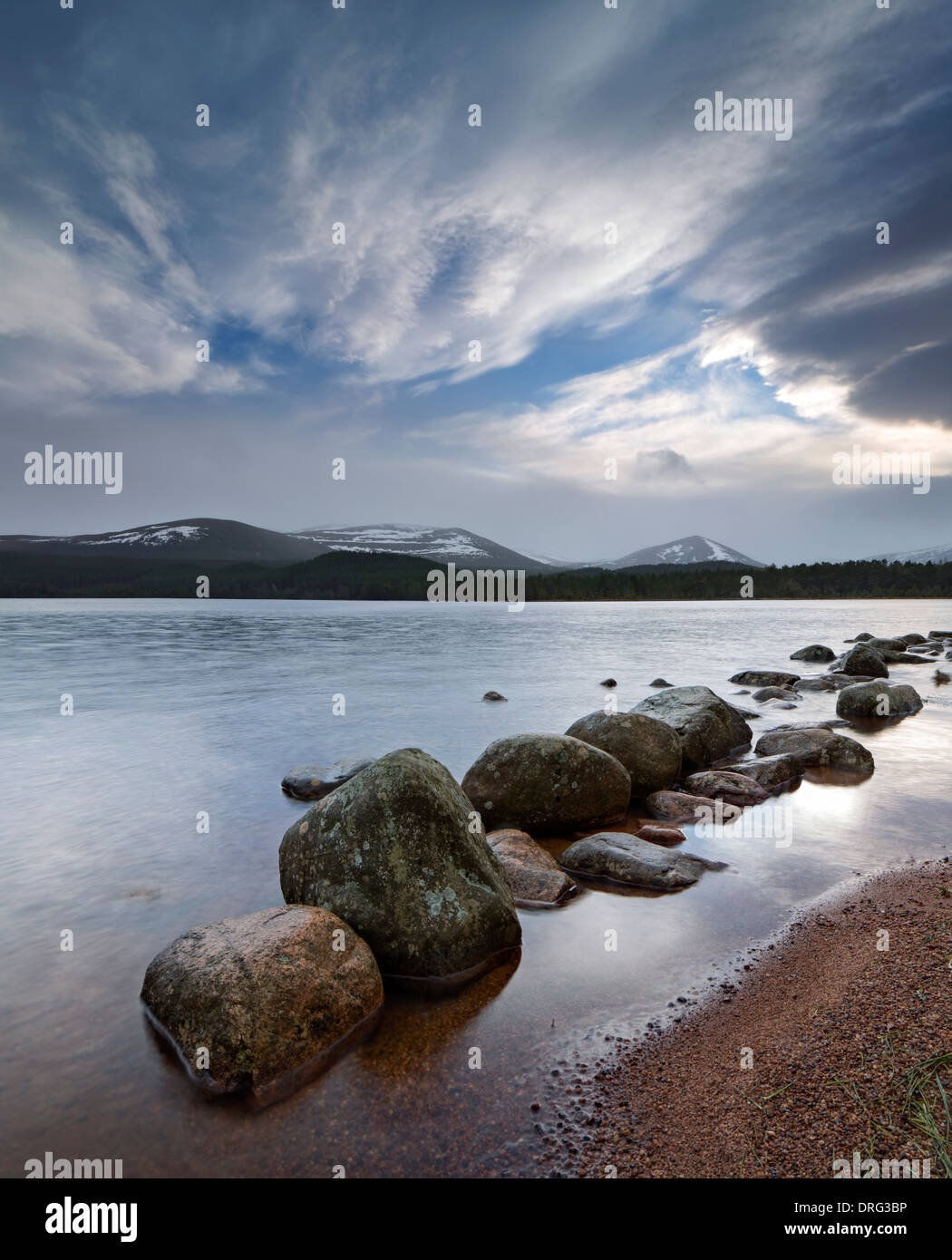 Dawn breaking over Loch Morlich and the Cairngorms in Glenmore Scotland. - Stock Image