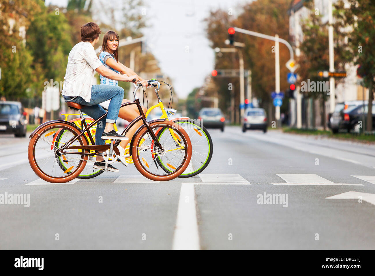 Young couple with bicycles on a zebra crossing, Osijek, Croatia - Stock Image