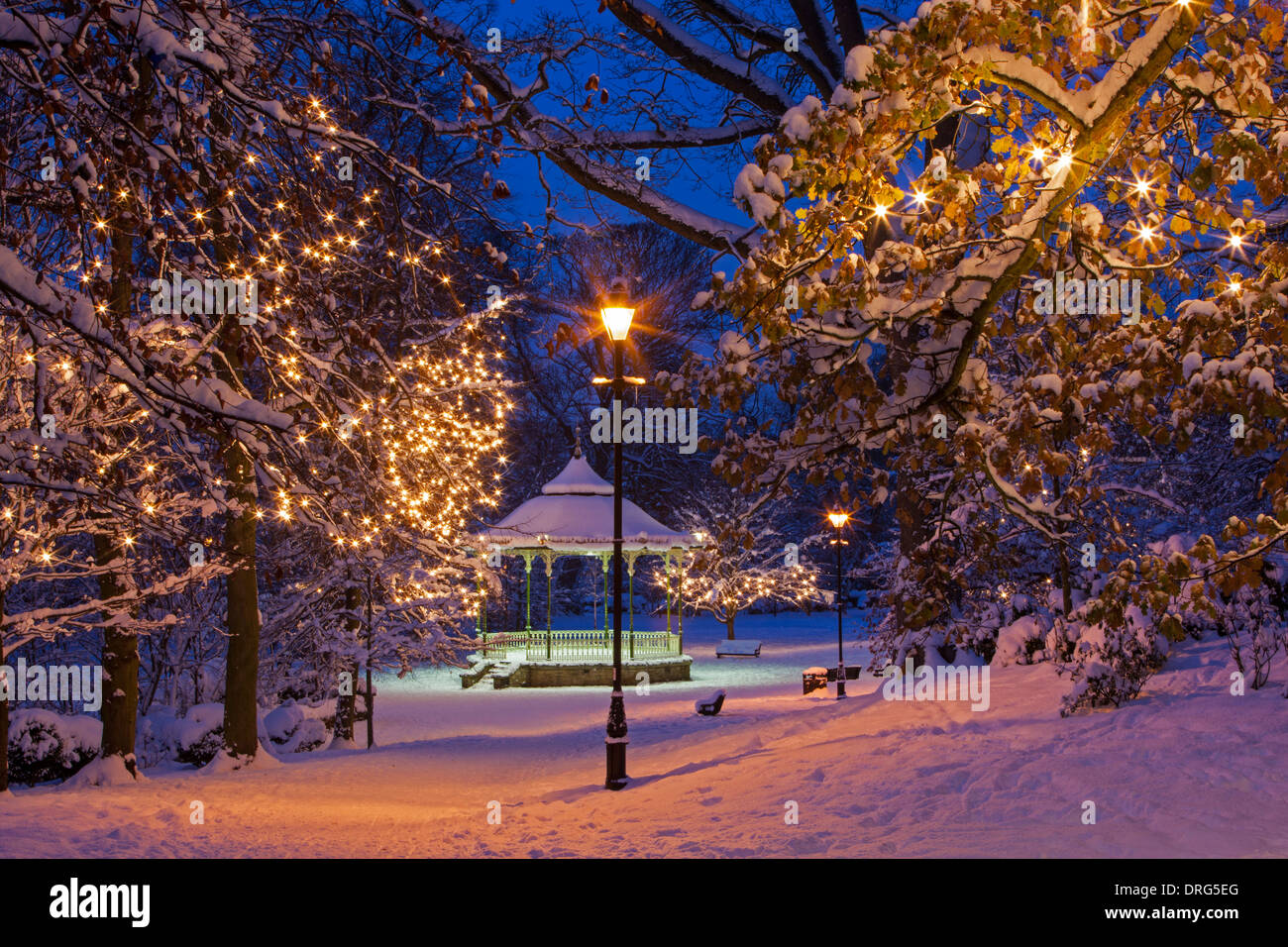 A night-time view of the Bandstand in Hexham in winter in Northumberland covered in snow illuminated by street lighting Stock Photo