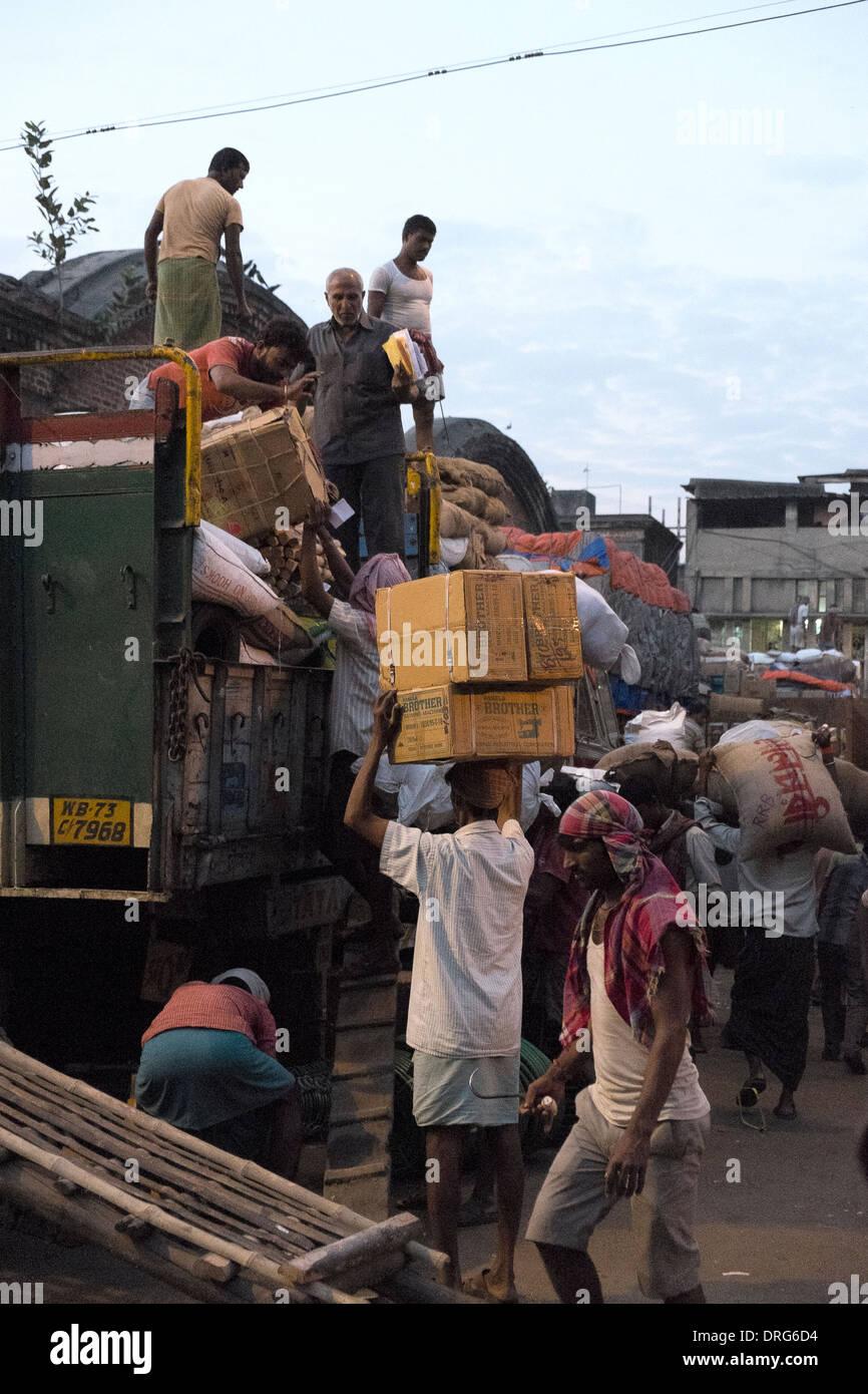 India, West Bengal, Kolkata, labourers loading and unloading goods near railway yard - Stock Image