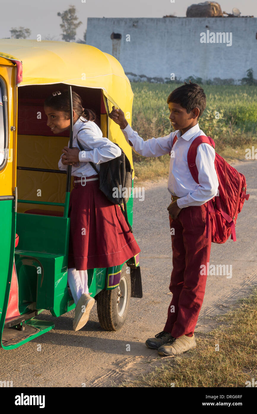 Brother and sister in school uniform getting in to auto rickshaw - Stock Image