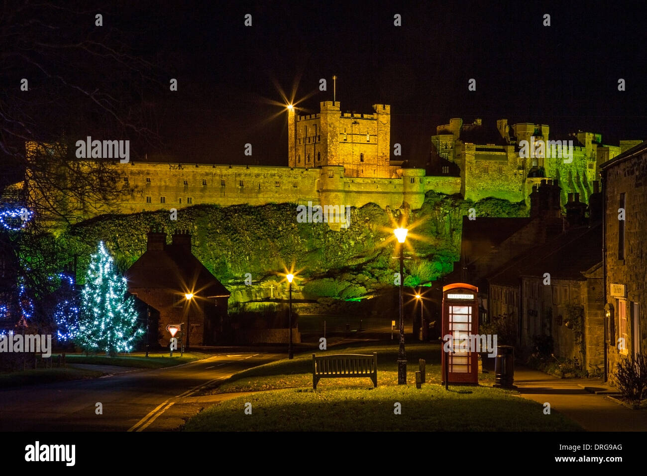 Bamburgh Castle in Bamburgh, Northumberland floodlit at night at Christmas time - Stock Image