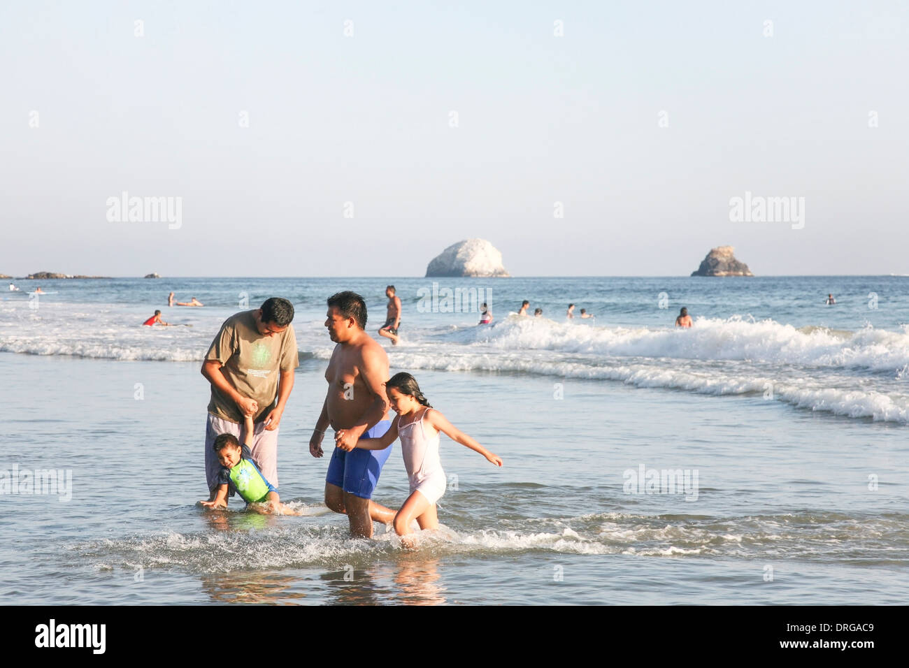 little Mexican girl walking in ocean holding tight to her Dad's hand as another father dangles his toddler son in the water - Stock Image
