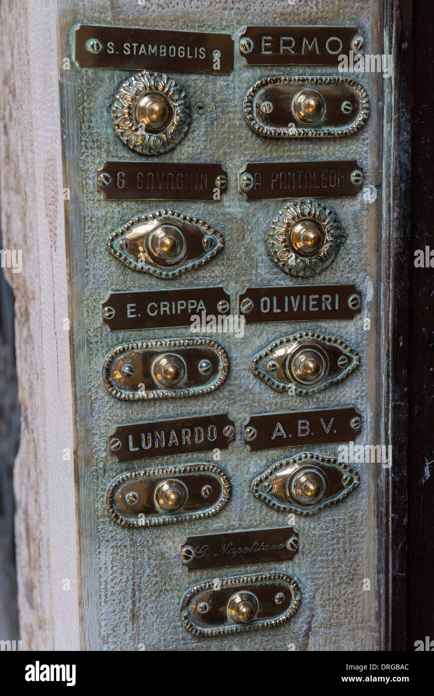 Brass Doorbell Buttons and Family Name Plates on an Entrance Panel to an Apartment Building, Venice, Italy Stock Photo
