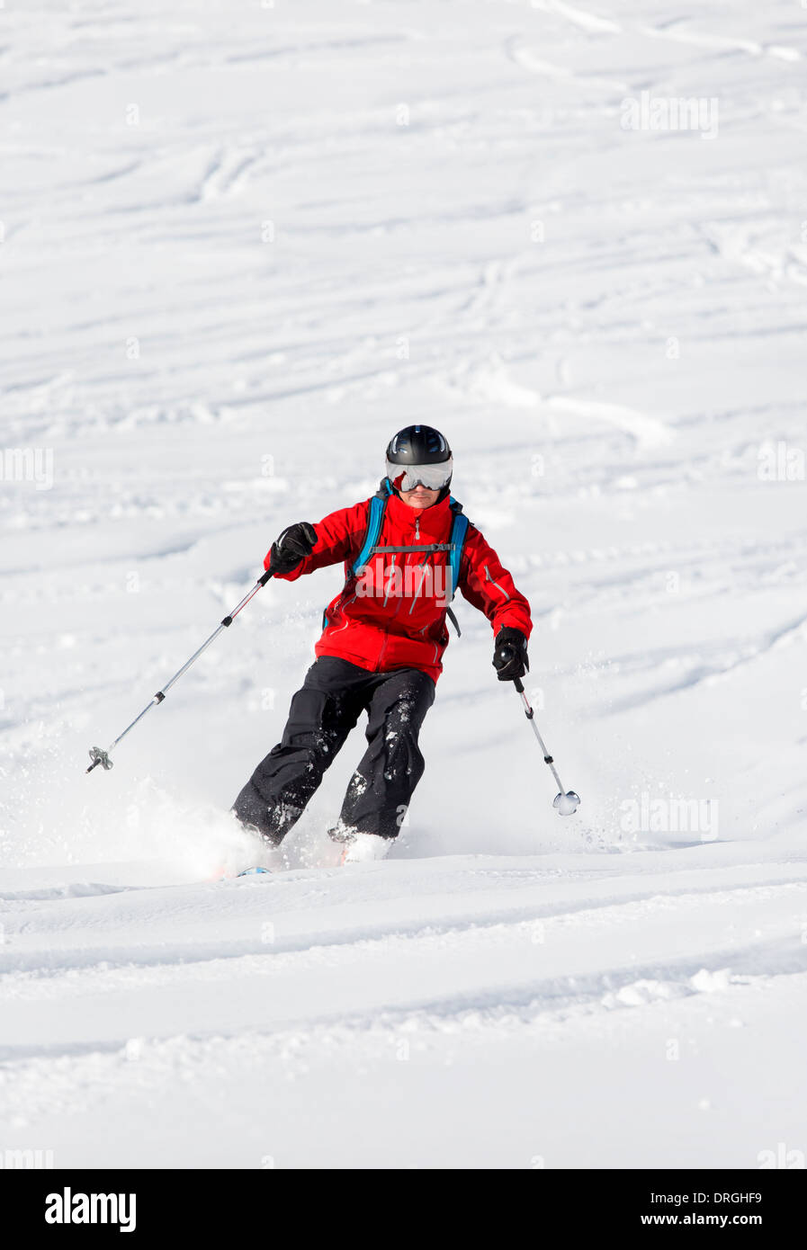 Male with visor helmet is skiing back country - Stock Image