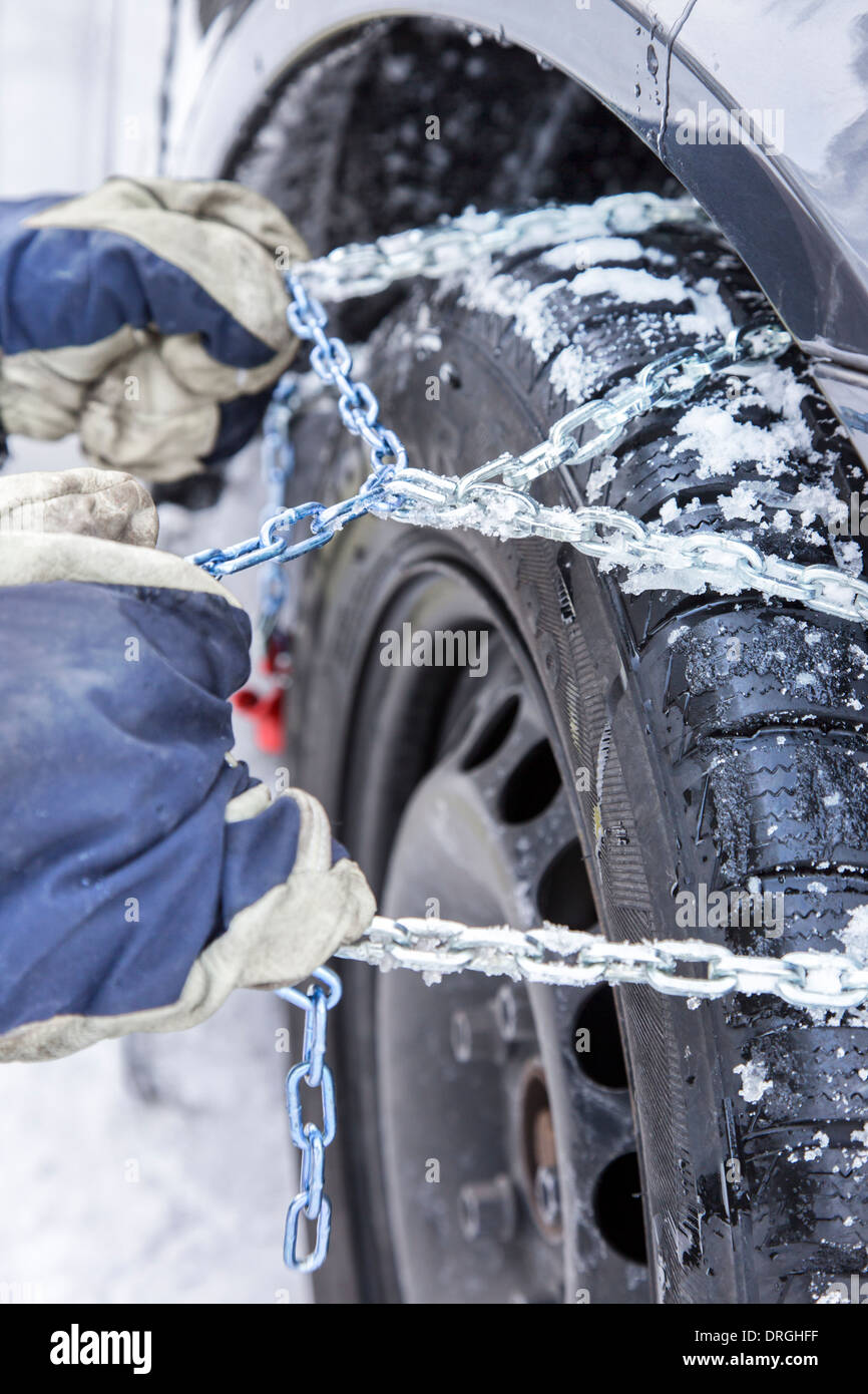 Car driver mounts snow chains on the tire of his car - Stock Image