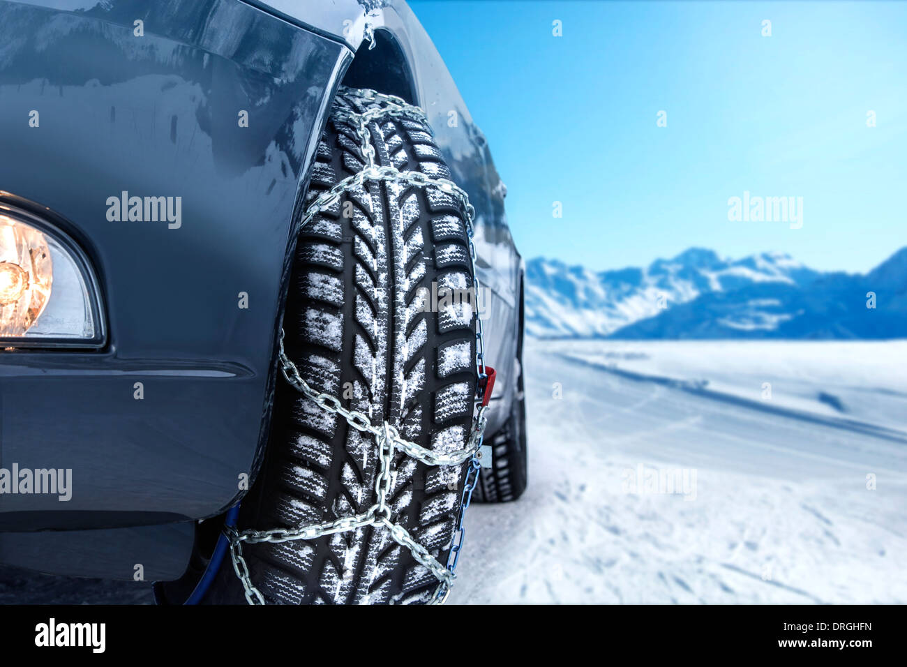 Car with mounted snow chains in wintry environment - Stock Image