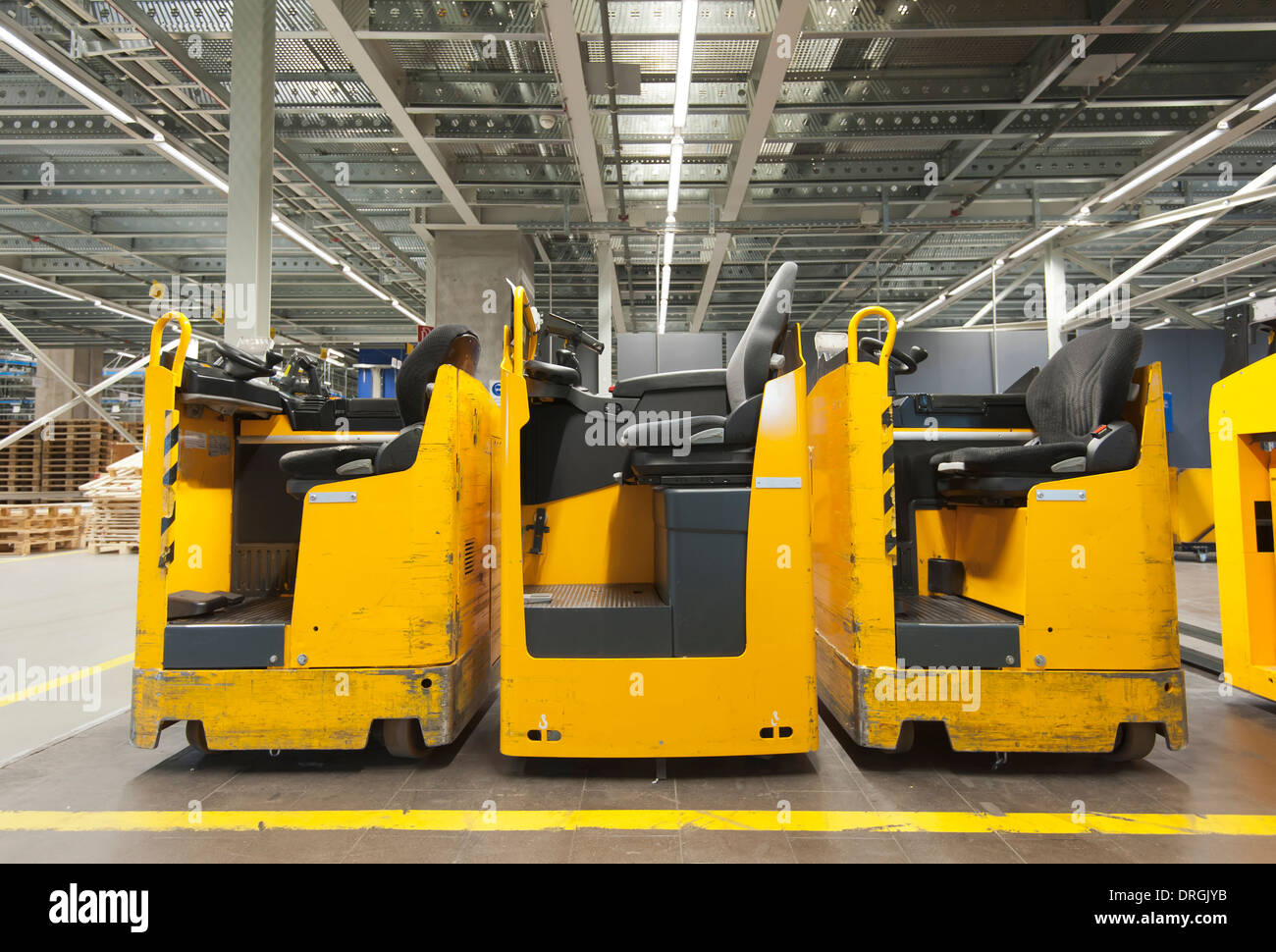 Three parked forklift in an industry warehouse - Stock Image