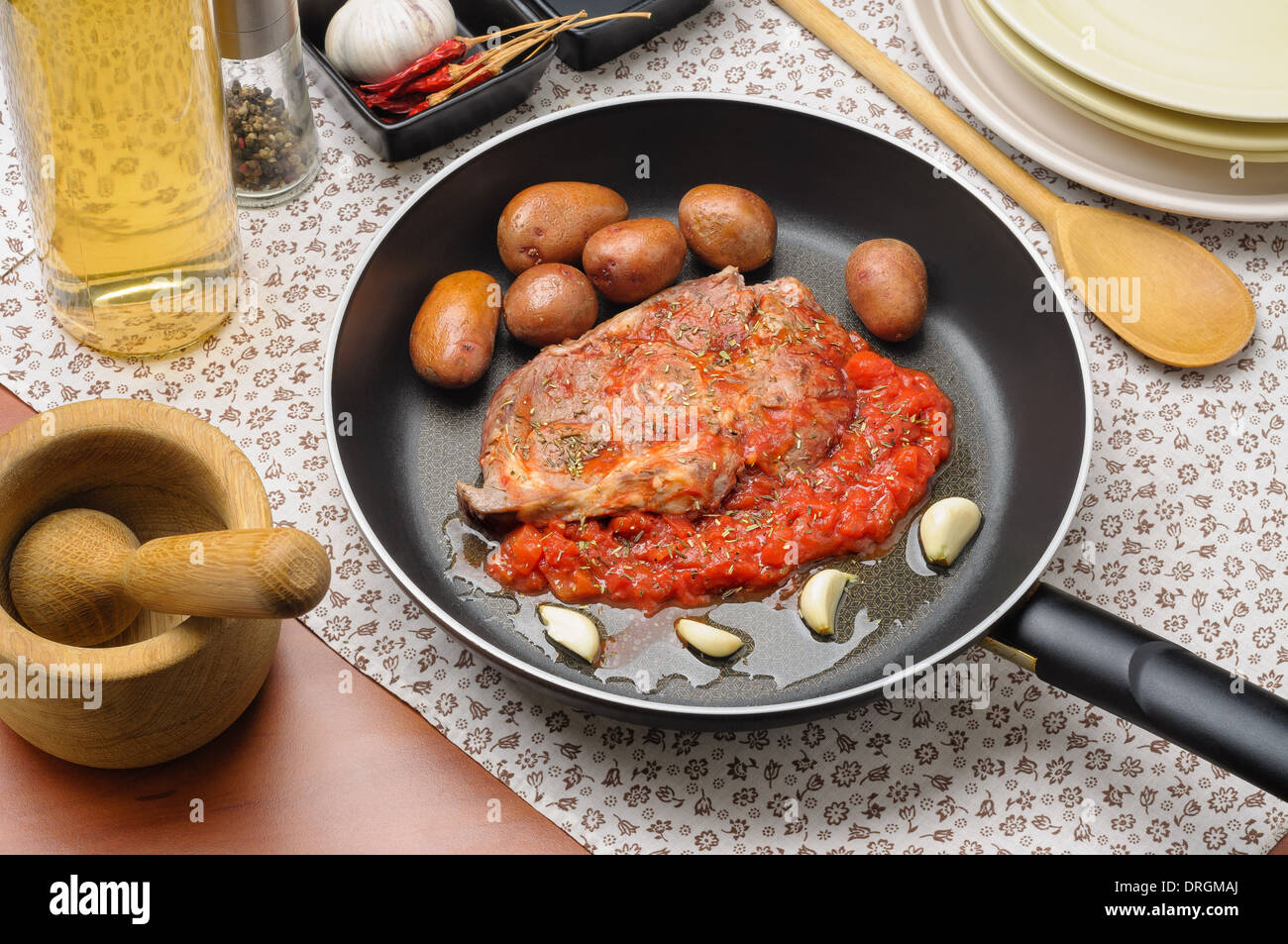 Preparation of ossobuco with tomato, garlic and provencal aromatic herbs, with small new potatoes - Stock Image