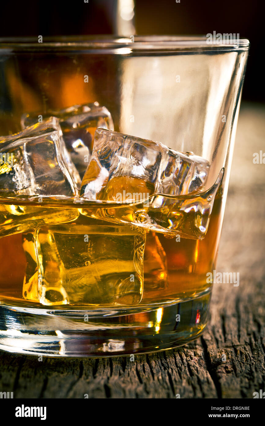 whiskey in glass with ice on wooden table - Stock Image