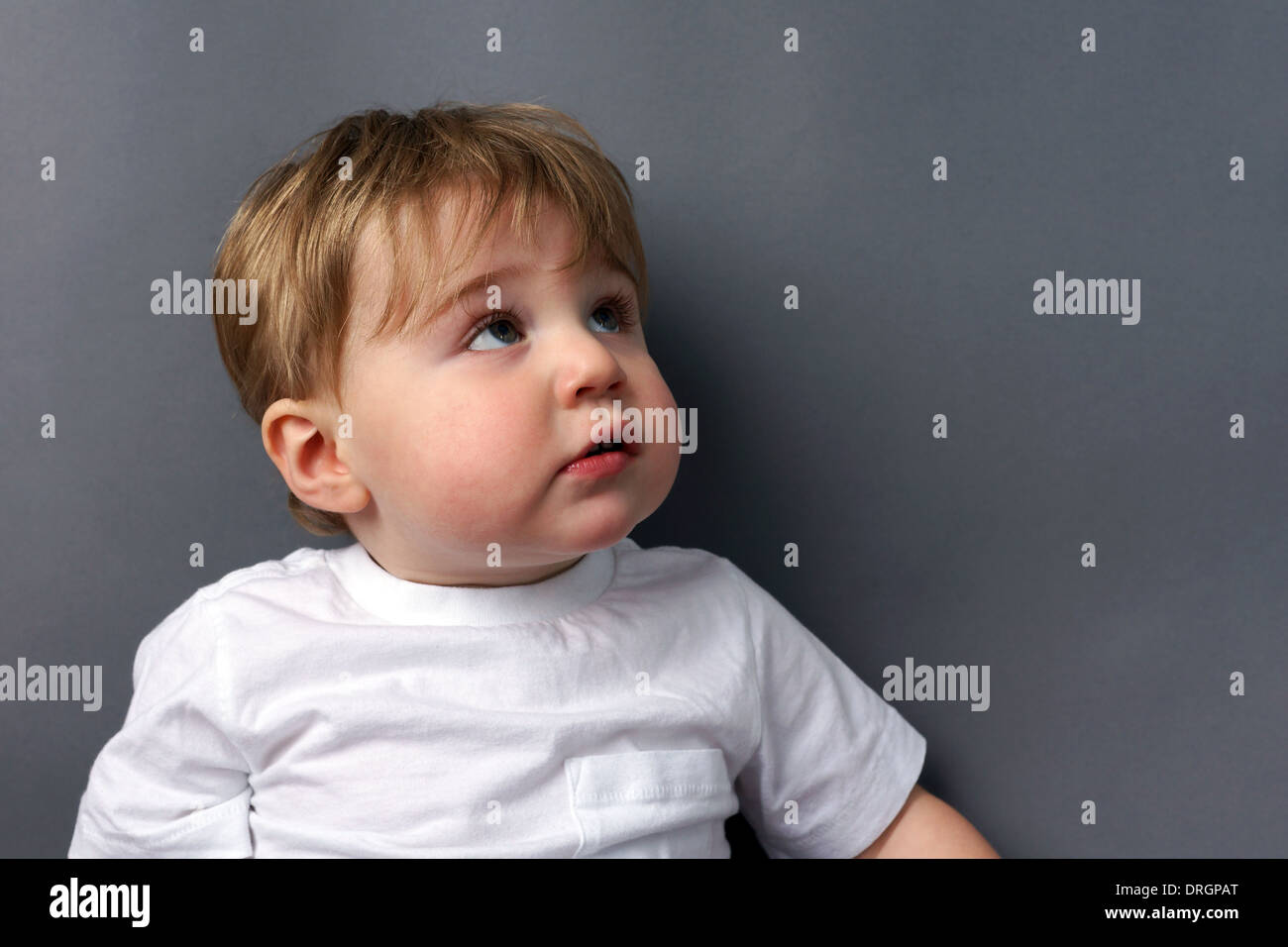 Cute little blond toddler boy looking up, unsure - Stock Image