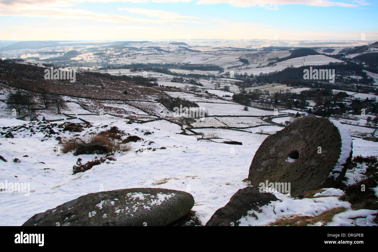 Snowfall over Curbar Edge and abandoned millstone looking across the Derwent Valley over Calver, Peak District NP, Derbyshire UK - Stock Image