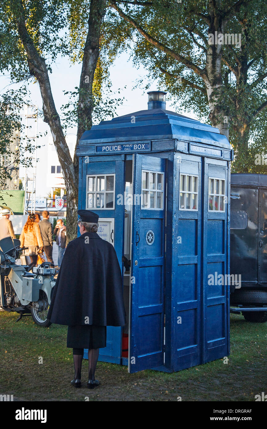 Woman standing beside a blue police telephone box at the Goodwood Revival 2013, West Sussex, UK - Stock Image