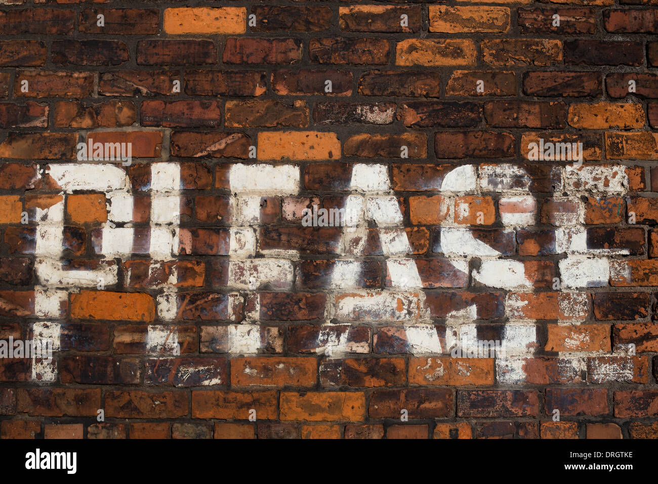 'Please' written on a brick wall with white paint - Stock Image